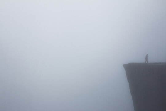 Man walking on cliff on foggy day in Norway