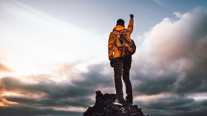 Hiker standing on the cliff mountain pointing the sky with fingers at sunset. Successful man on the...