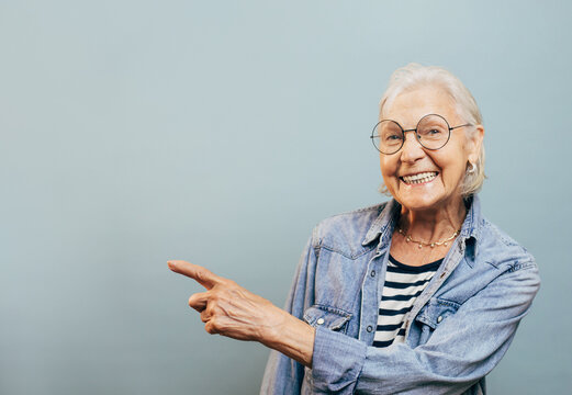 Nice friendly old woman with white hair and round glasses wants to show something to you. Stylish old ages concept. Isolated over blue background. Jeans jacket and striped shirt.