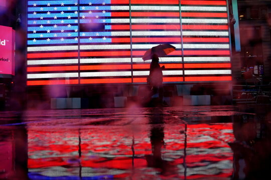 Pedestrian walks in the rain past a U.S. flag displayed in Times Square in New York City