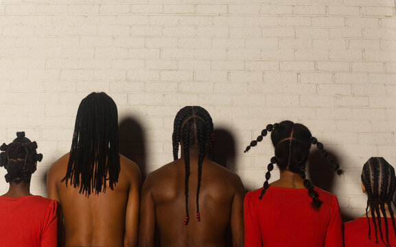 Rear view of women with variety of hairstyles standing indoors
