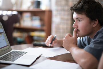 male college student doing schoolwork at home in remote set up