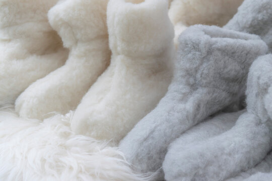 Soft white and beige fluffy background with woolen rugs and sheep fur socks. Winter chill out concept. Cozy Nordic Christmas in Hygge style. Comfortable woolen clothes for autumn and winter chill.