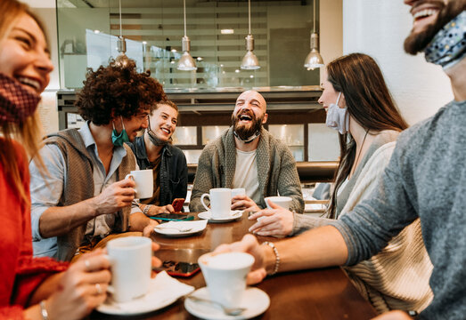 Group of happy friends with face mask drinking espresso at coffee house  - Young millenial having fun together at bar cafè - New normal lifestyle concept - Focus on man in the middle