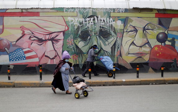 Women walk past a graffiti depicting U.S. President Donald Trump, the Pachamama (Mother Earth) and Chinese President Xi Jinping, in El Alto