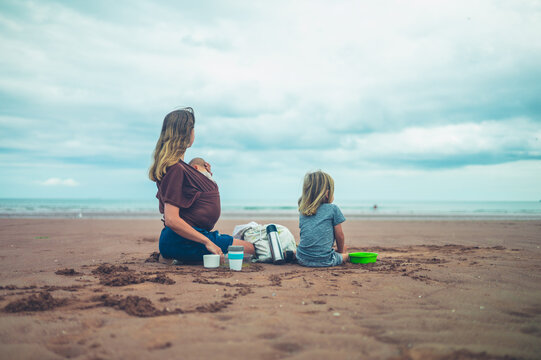 Mother with baby and preschooler having picnic on the beach