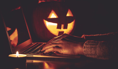 Halloween evening at the computer. Woman talking on the feast of Halloween on the internet....