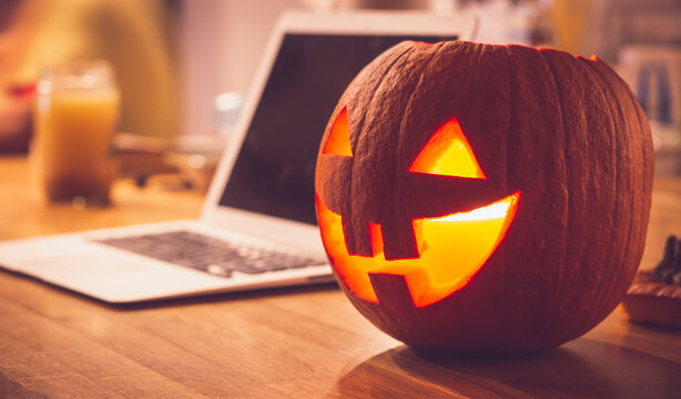 Lonely evening on Halloween. Laptop and lit pumpkin candle at home on the table. Concept of spending Halloween during the period of people's isolation during the coronavirus.
