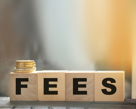 Coin stack and wooden blocks with the fee text. Fee Finance and Money concept. Copyspace for text