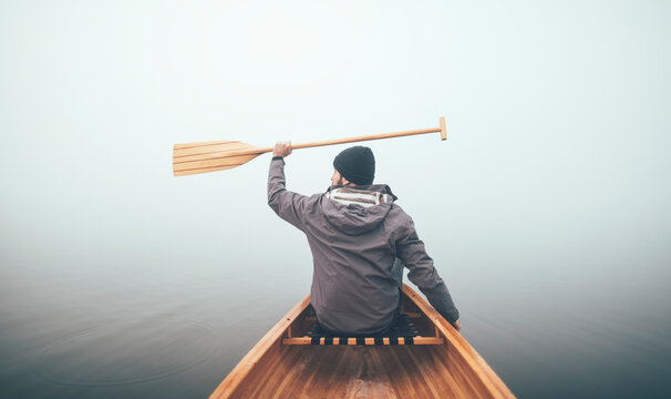 Active man holds canoe paddles high on the misty lake