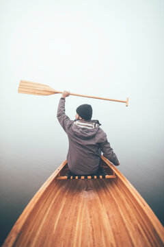 Rear view of active man holds canoe paddles high in the winter