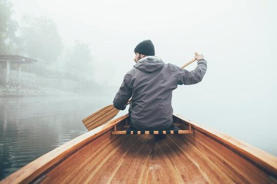 Man paddling canoe on the misty lake