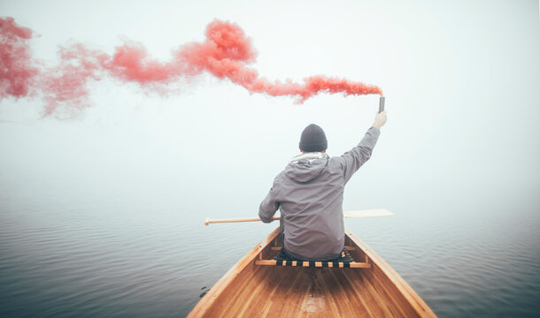 Man in canoe using smoke bomb for signal his position