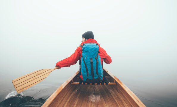 Raer view of the canoeist paddling on the hazy lake