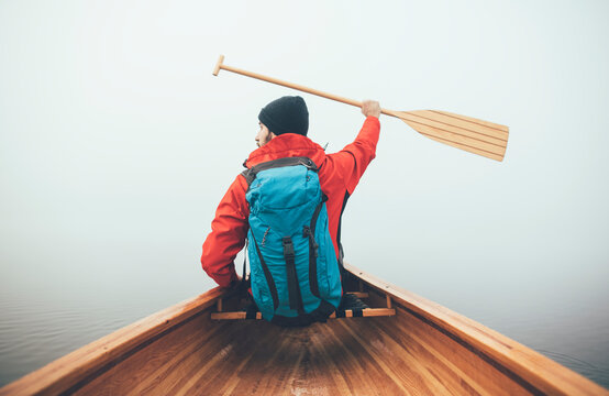 Rear view of active man paddling canoe in the winter