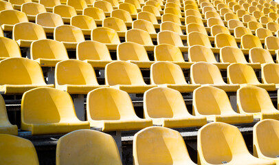 yellow tribunes. seats of tribune on sport stadium. empty outdoor arena. concept of fans. chairs for audience. cultural environment concept. color and symmetry. empty seats. modern stadium