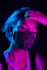 Young beautiful fashionable woman in protective mask with rhinestones dancing in night club. Neon colorful light. Close-up portrait of fashion model.