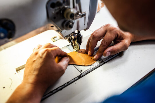 The master sews leather garments at the factory