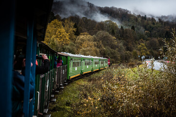Retro Train Trough Wilderness of Bieszczady Mountains in Poland at Autumn. Dramatic Weather and Moody Toned Colors.