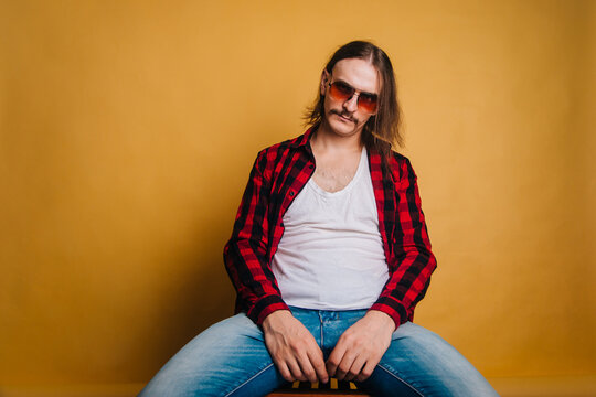 Attractive man with long hair and a mustache in a red 80s disco plaid shirt, sitting on a chair against a yellow background. Retro studio photo. Guy in fashionable sunglasses