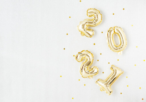 Happy New year 2021 celebration. Gold foil balloons numeral 2021 on silver background.