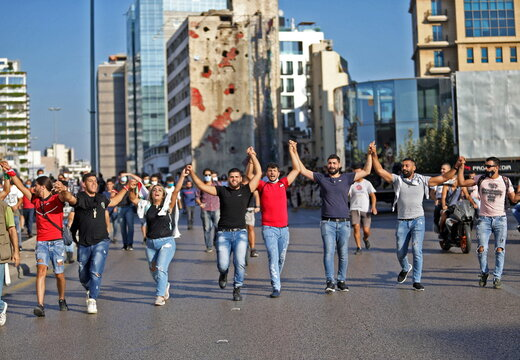 People hold hands as they march during a demonstration in Beirut