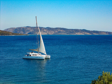 White catamaran yacht sailing boat alone on blue sea and cloudless sky