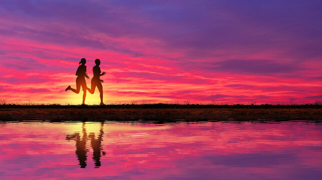 Young couple of girlfriends run at sunset