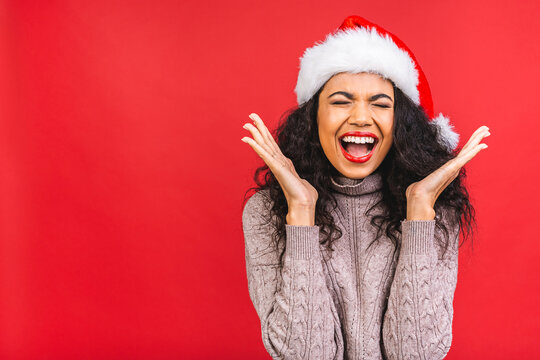 Portrait of beautiful african american female woman model wearing santa hat isolated over red background.