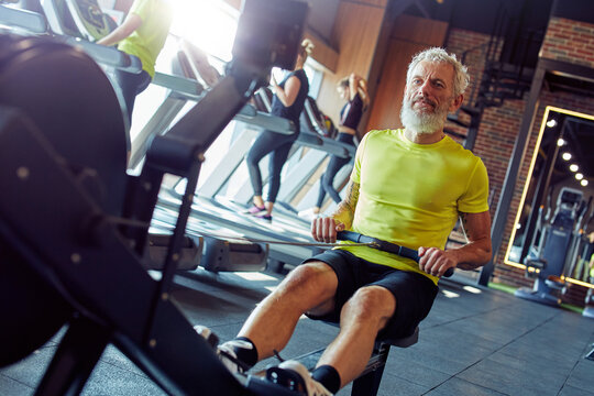 Staying fit and healthy. Strong mature athletic man in sportswear exercising on rowing machine at gym