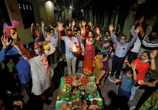 Hindu devotees raise their hands as they pray to Hindu goddess Durga in an alley of a residential area on the first day of Navratri festival in Ahmedabad