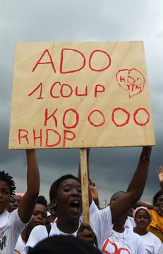 A supporter of presidential candidate Alassane Ouattara of the ruling RHDP coalition party holds a sign during a campaign rally for the October 31, 2020 presidential election, in Abidjan