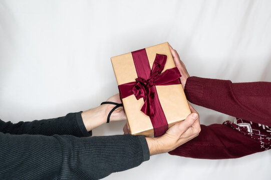 two people fight for a present with red ribbon