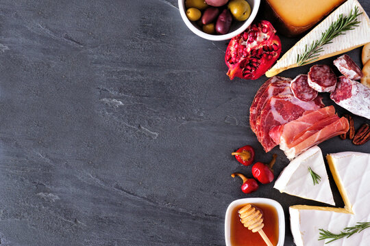 Assorted cheese and meat appetizers. Above view side border on a dark slate background with copy space.