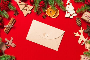 Wall Mural - Top view of envelope on red background. New Year decorations. Christmas holiday concept
