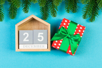 Wall Mural - Top view of wooden calendar, gift box and fir tree on colorful background. The twenty fifth of December. Christmas time with copy space