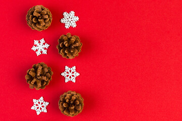 Wall Mural - Top view of holiday composition made of pine cones and white snowflakes on colorful background. Winter time and Christmas concept with copy space