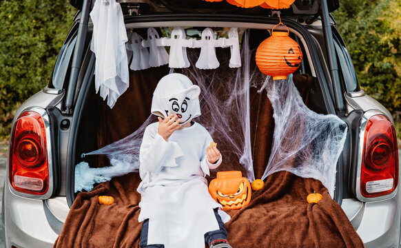 Trick or trunk. Trunk or treat. Happy child in ghost costume having fun celebrating Halloween party in decorated car trunk. New trend and alternative safe outdoor celebration of traditional holiday.