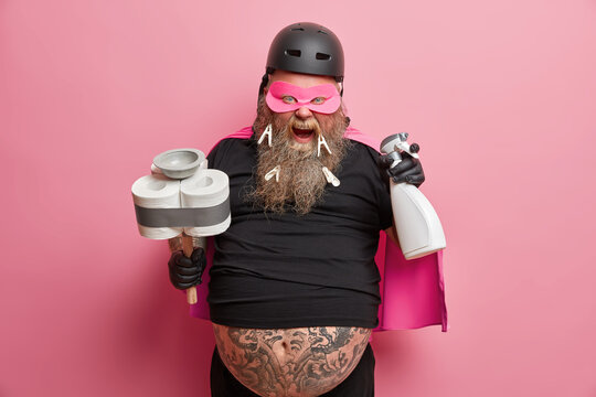 Super cleaning concept. Funny bearded janitor ready to clean up room holds plunger and detergent wears costume exclaims loudly poses against pink background. Housekeeping cleanliness hygiene concept