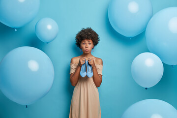 Upset dark skinned woman with curly hair holds blue high heel shoes prepares for party poses...