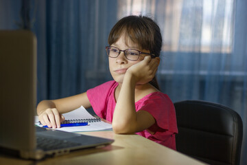 Tired child in front of the computer. Online education for kids. Tired and bored teenage girl is studing.