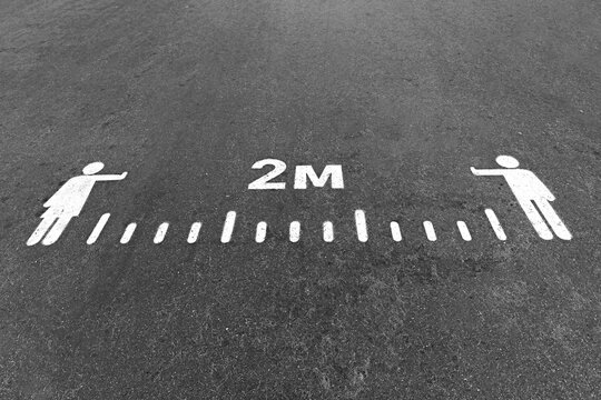 White painted 2 meters social distance sign on an asphalt road, pavement