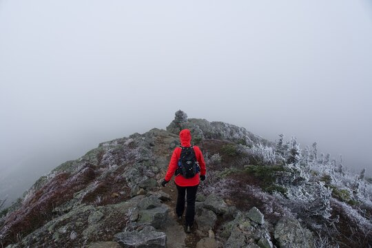 Lone woman hiking over a mountain ridge on icy rocks in the clouds
