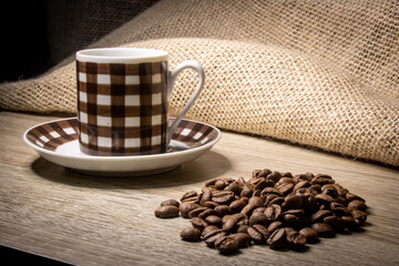 cup of coffee and grain coffee beans on jute background in Brazil