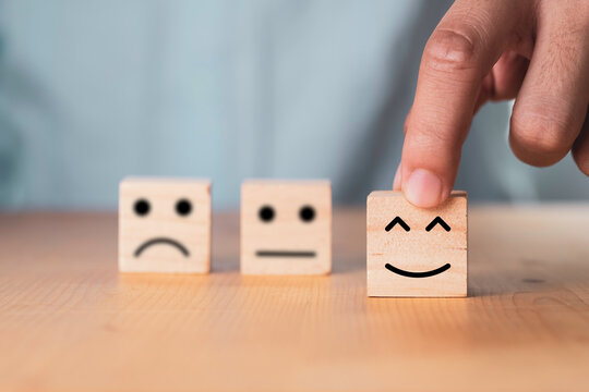 Select emotion or mood concept , Hand holding smile face  or happy face which print screen on wooden cube block.