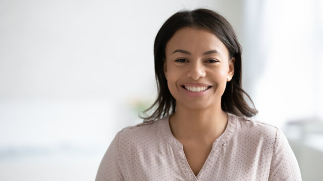 Narrow wide panoramic view headshot portrait of smiling African American young woman pose at home. Banner profile picture of happy biracial female renter or tenant look at camera. Copy space.