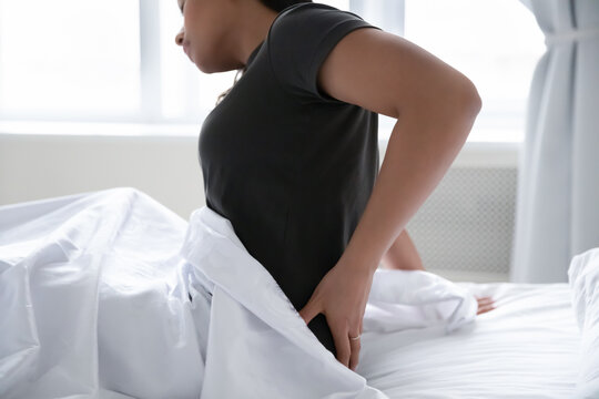 Close up of unhealthy African American woman sit in bed hold massage lower back suffer from spasm or strain. Unwell sick biracial female suffer from muscle pain or ache sleeping in incorrect posture.