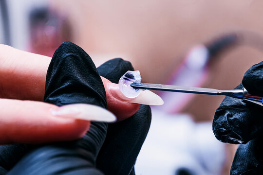 The manicure master applies a base layer of Poly-gel to the nail with a metal spatula. The brush distributes the gel over the entire surface of the nail. Close-up , selective focus