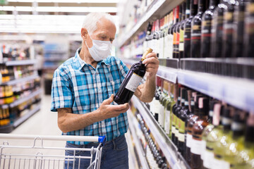 mature european man wearing mask with covid protection chooses bottle of alcohol in supermarket