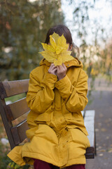 Cute girl in yellow coat sitting on the bench. The girl holds an armful of leaves